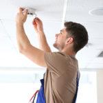Electrician checking a ceiling smoke alarm