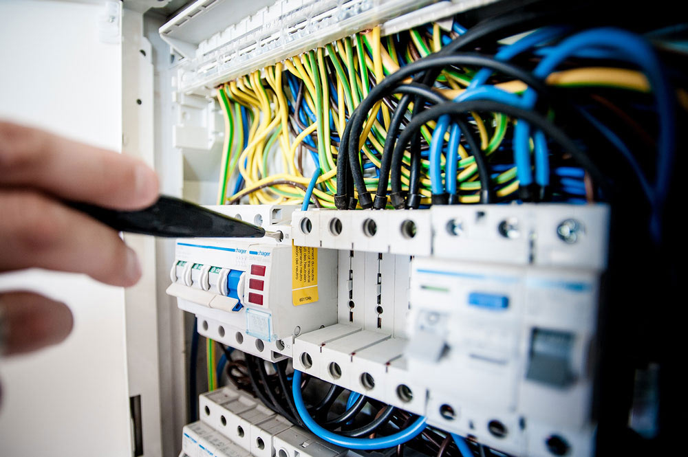 Close up of a hand with a test probe carrying out an electrical test on a consumer unit